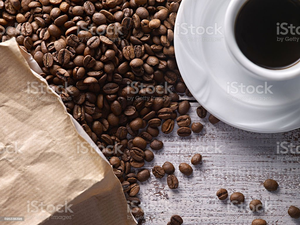 Coffee cup and coffee beans spills out of the bag stock photo