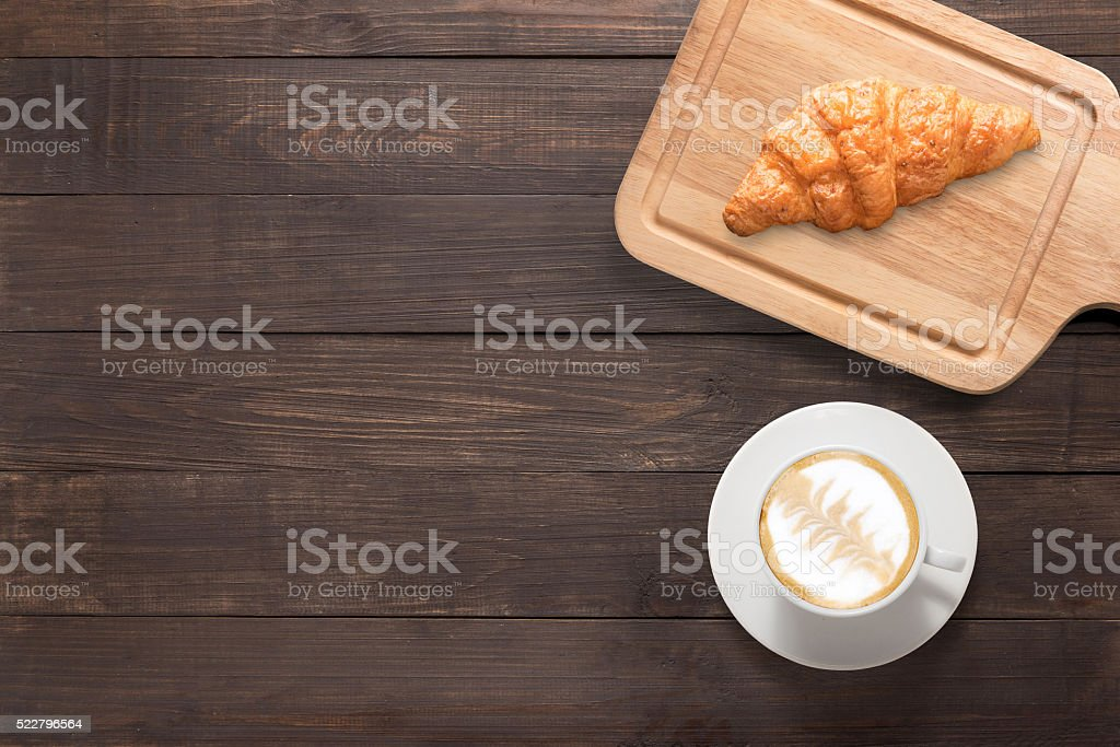 Coffee cup and fresh baked croissants on wooden background. stock photo