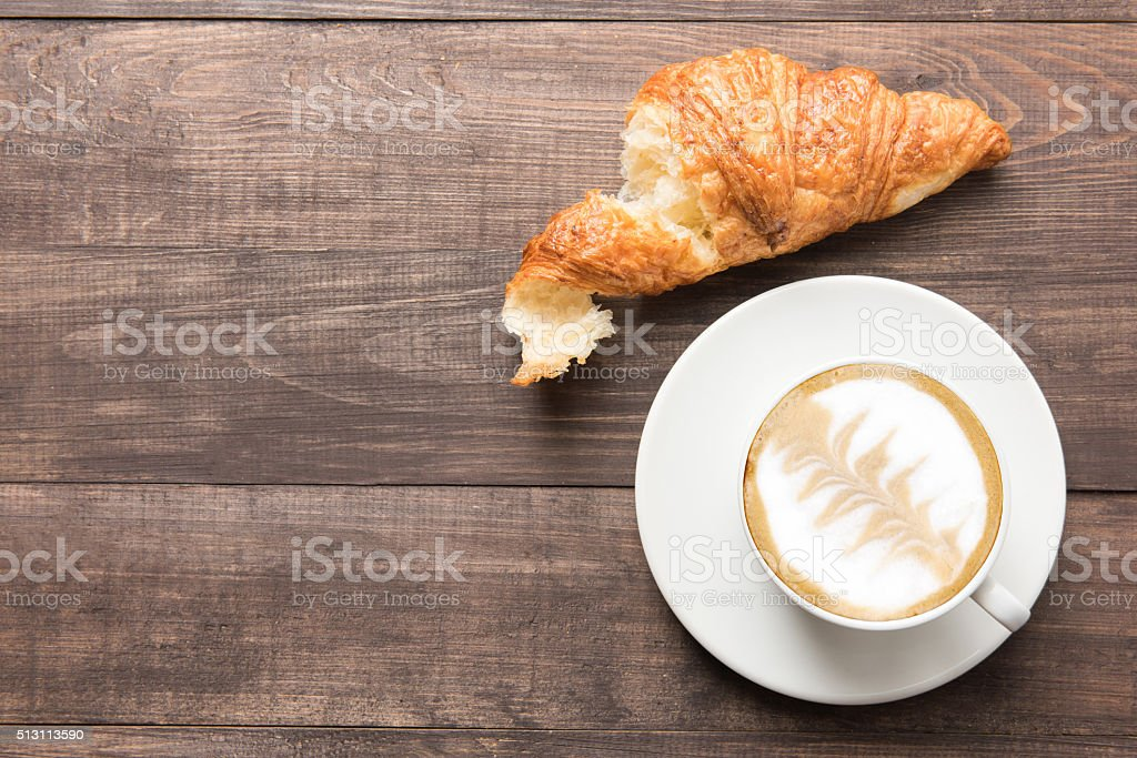 Coffee cup and fresh baked croissants on wooden background. Top stock photo