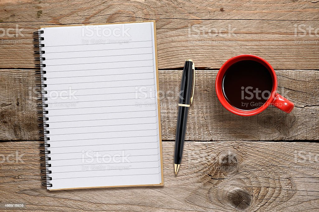 Coffee cup and notepad with pen stock photo