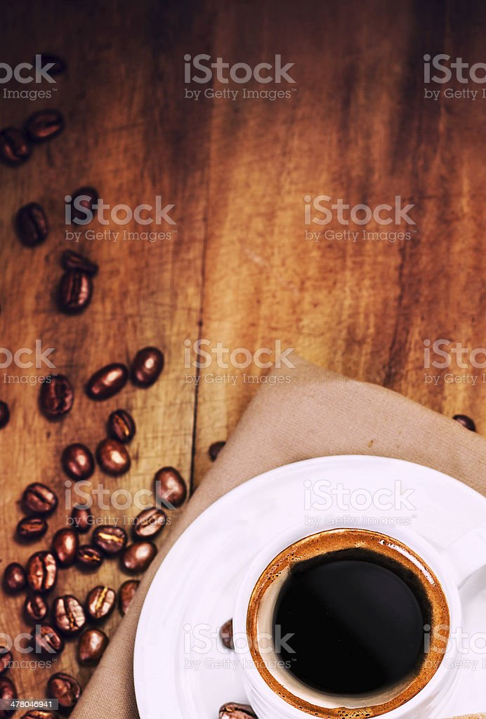 Coffee cup and roasted cofee beans  on wooden  brown background royalty-free stock photo