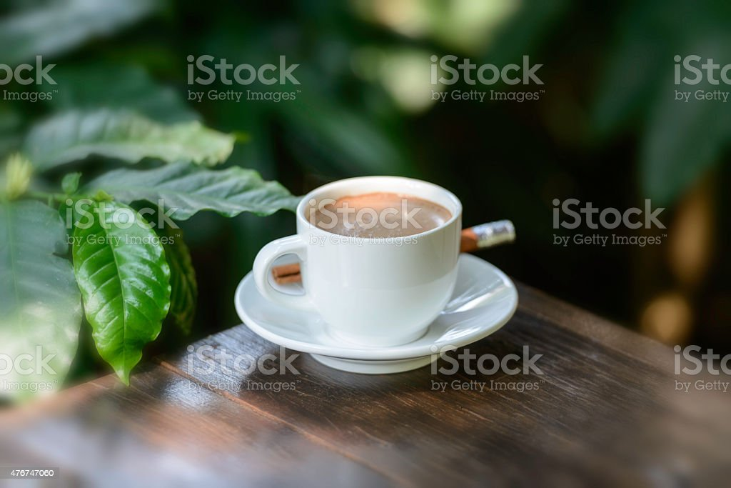 Coffee cup and saucer on a wooden table. Dark background. royalty-free stock photo