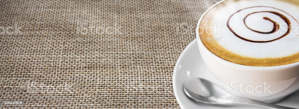 Coffee cup and saucer on sackcloth background stock photo