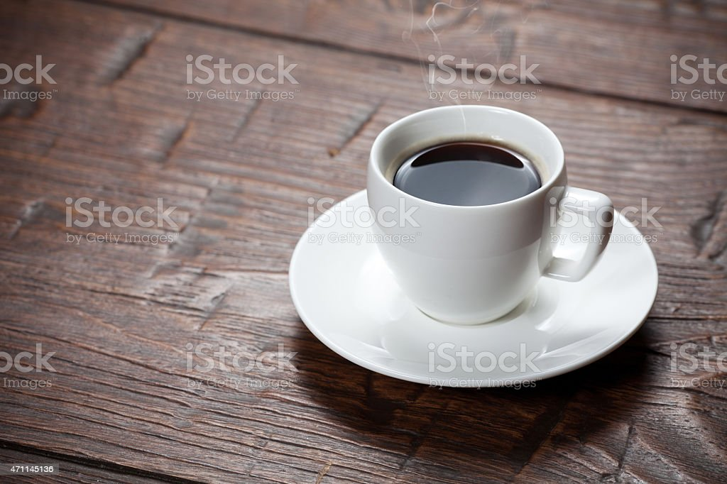 Coffee cup and saucer on wooden table stock photo
