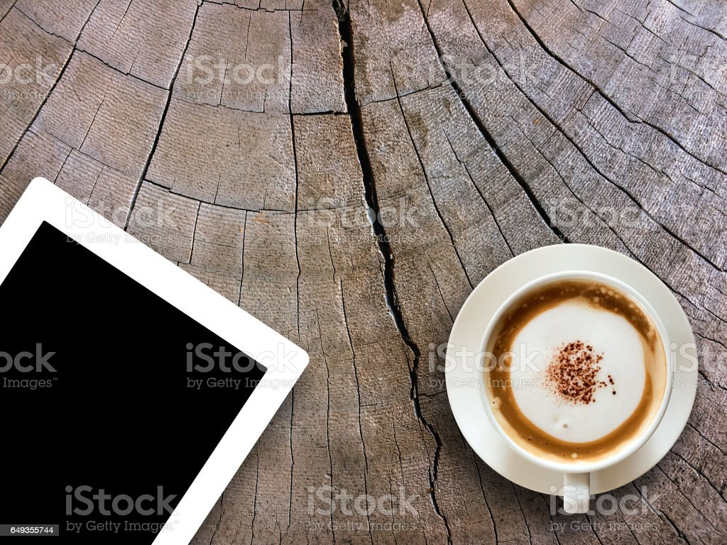 Coffee cup and tablet on wooden table background textured.Technology concept. stock photo