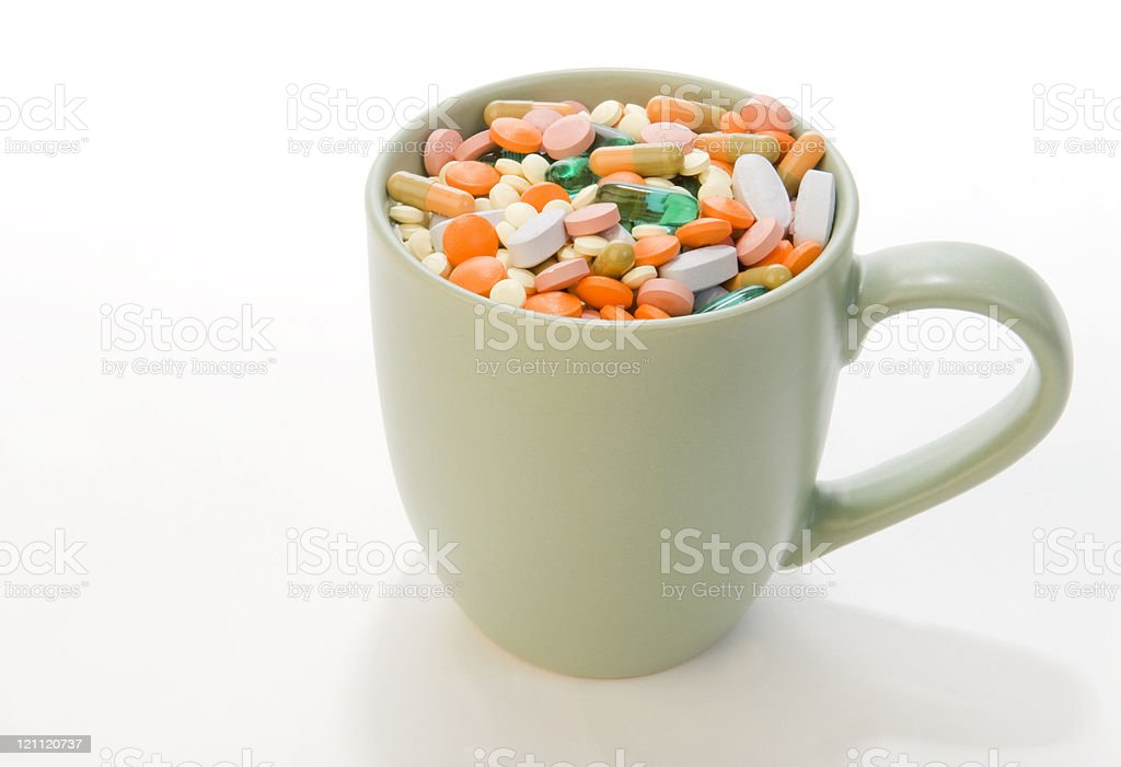 Coffee cup filled with pills stock photo