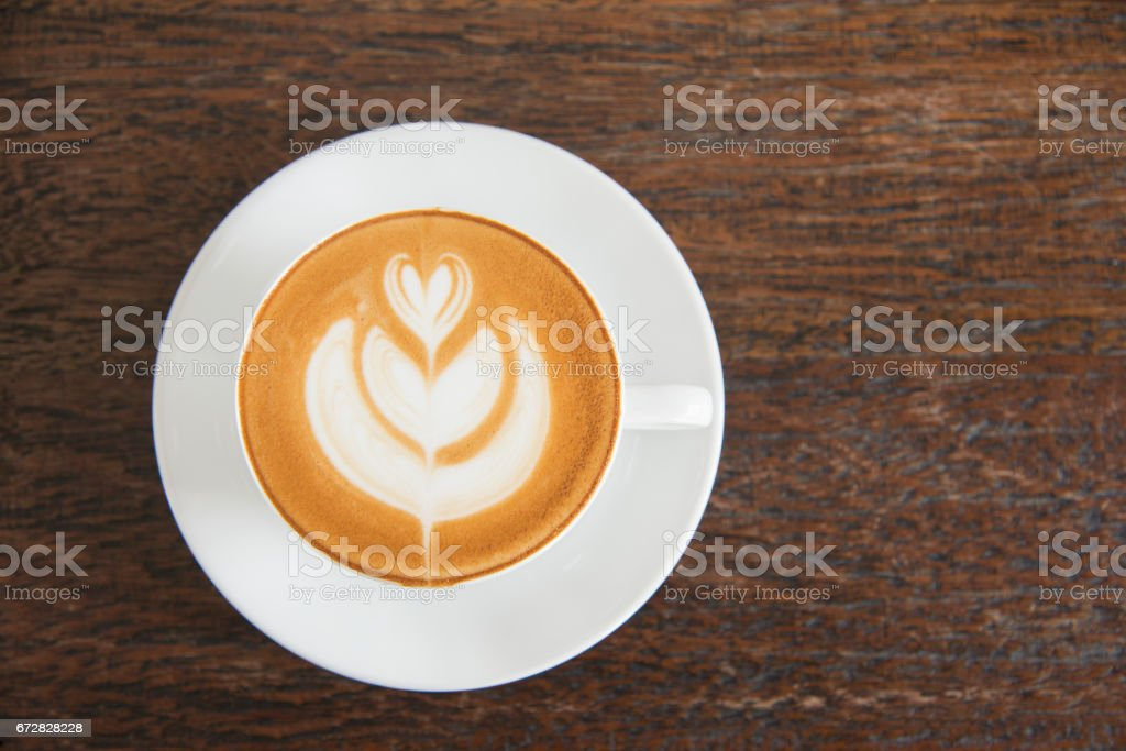Coffee cup latte art with hearth shape foam top view on wooden table background in coffee shop stock photo