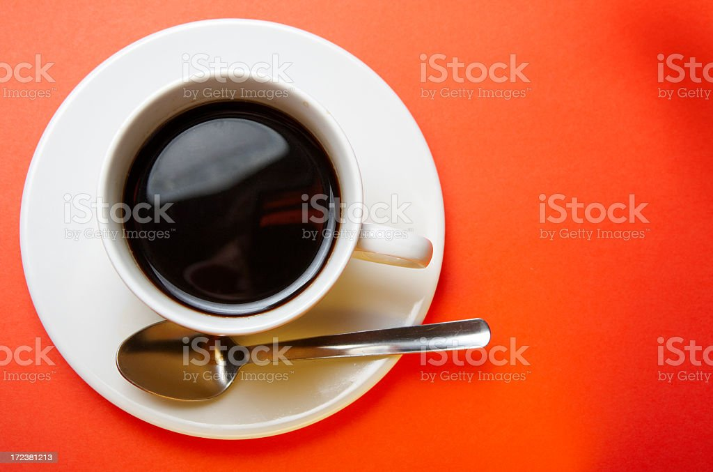 A coffee cup on a plate set against an orange background stock photo
