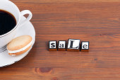 Coffee cup on a wooden table and text - Sale