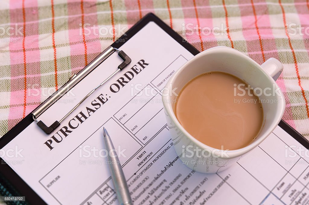 Coffee cup on purchase order form stock photo