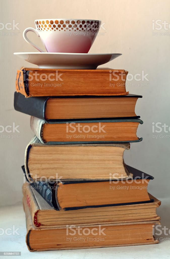 coffee cup on stack of old books stock photo