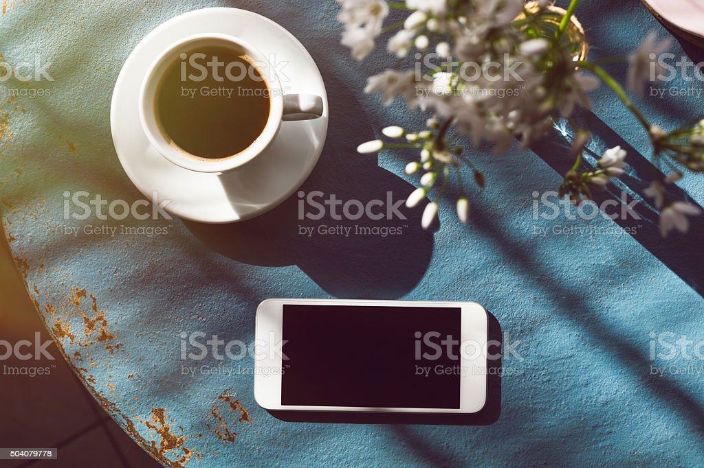 Coffee Cup on Table and Mobile Phone stock photo
