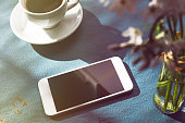 Coffee Cup on Table and Mobile Phone