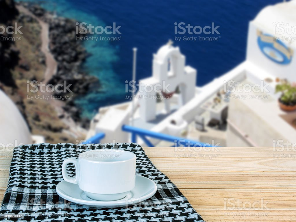 Coffee cup on wooden table top over mediterranean seascape background stock photo