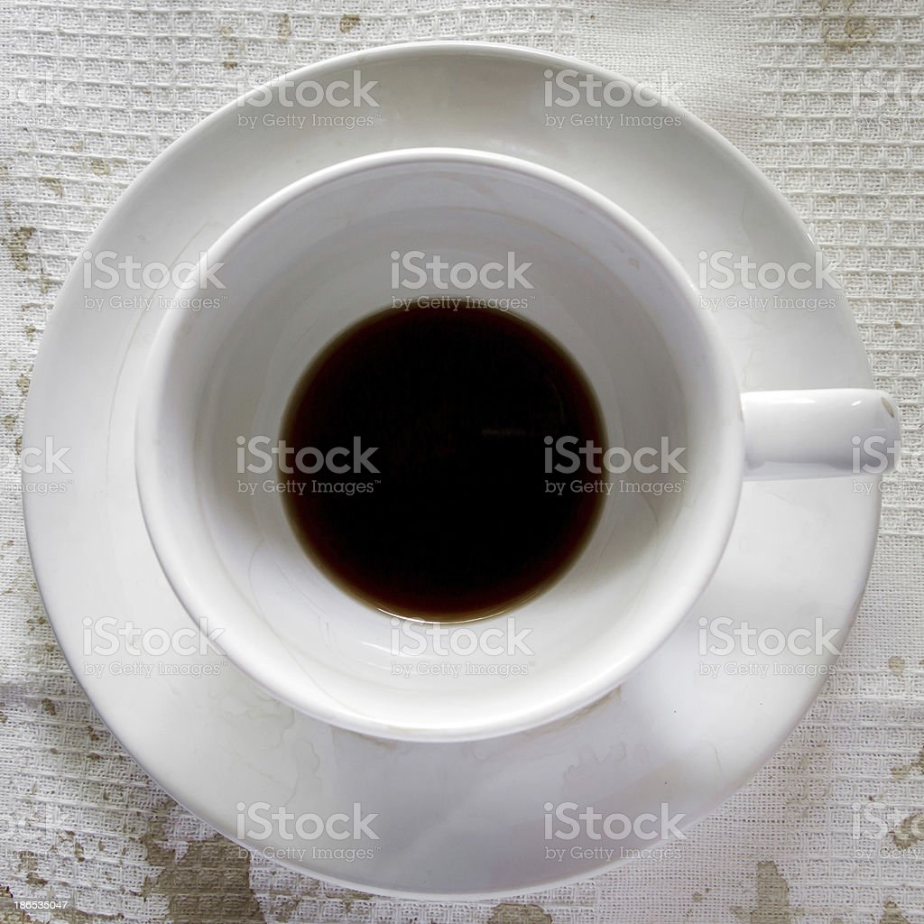 Coffee cup over white tablecloth background. Dregs in the bottom royalty-free stock photo