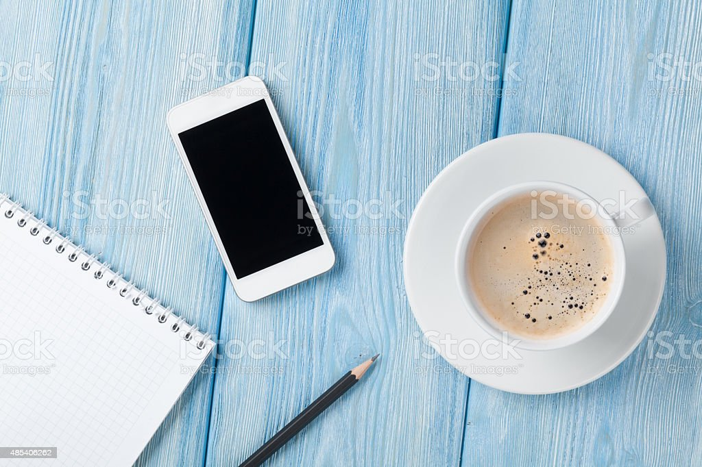 Coffee cup, smartphone and blank notepad on wooden table backgro stock photo