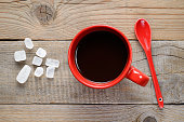 Coffee cup, spoon and rock sugar on wooden table