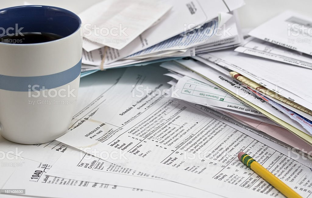 Coffee cup, stains and pencil on Tax Forms stock photo
