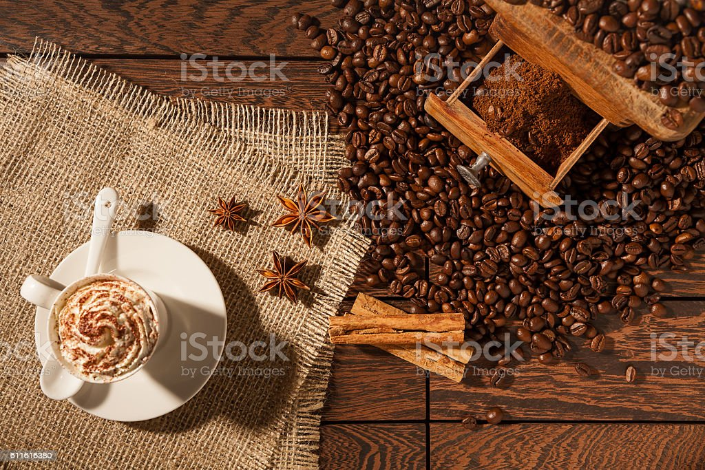 Coffee cup, star anise, cinnamon sticks and coffee-beans stock photo