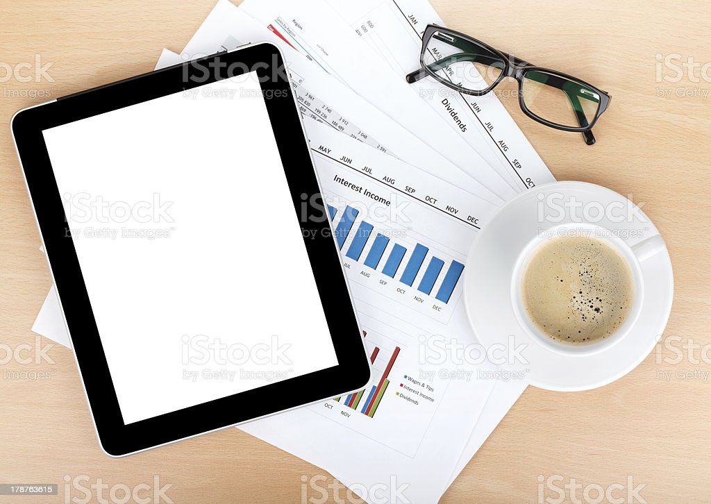 Coffee cup, tablet over papers with numbers and charts royalty-free stock photo