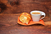 Coffee cup with a croissant isolated on wooden table