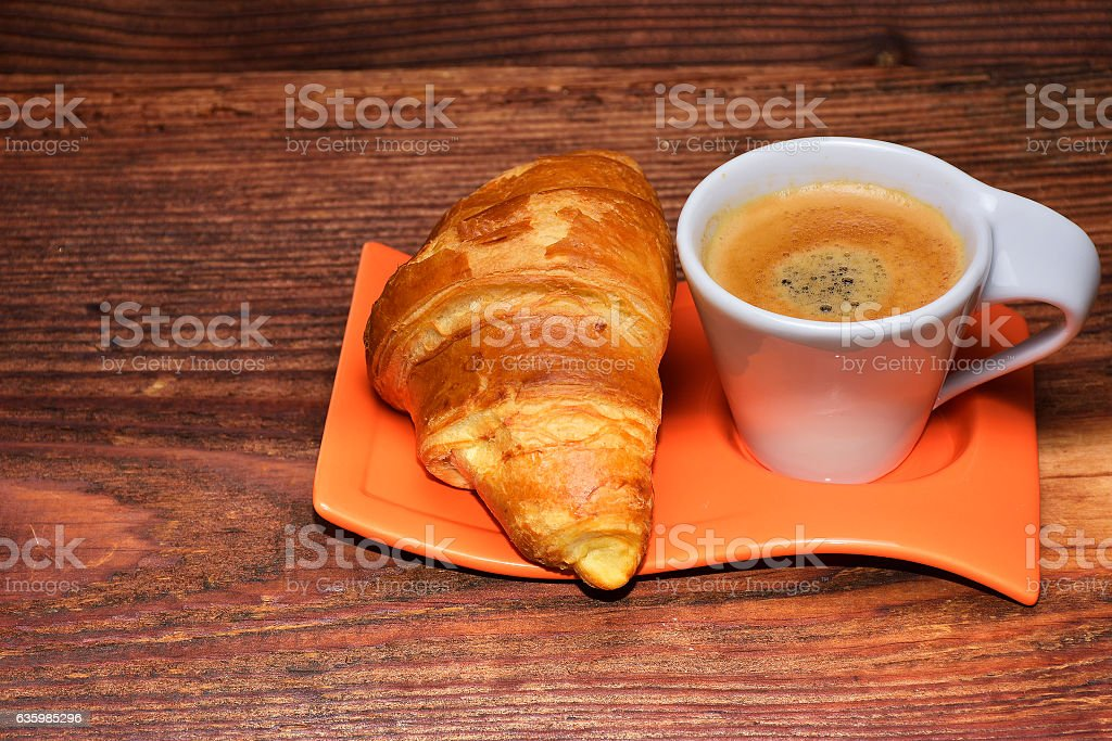 Coffee cup with a croissant isolated on wooden table stock photo