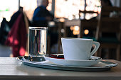 Coffee cup with a glass of water - stock image