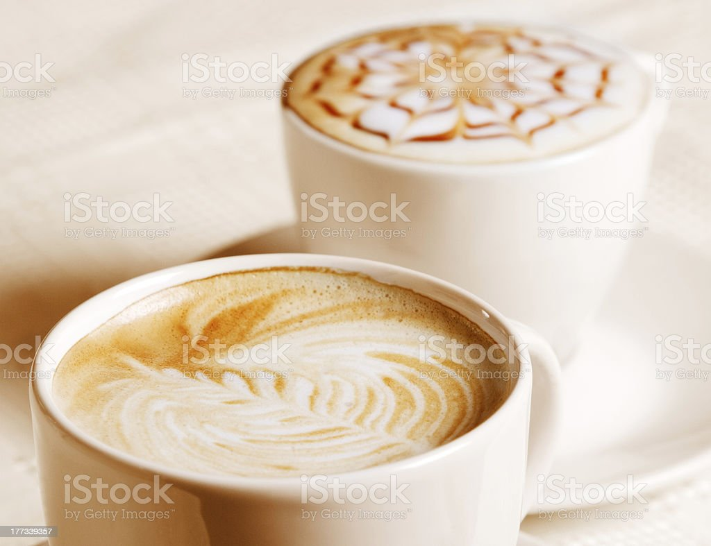 Coffee cup with artistic cream decoration royalty-free stock photo