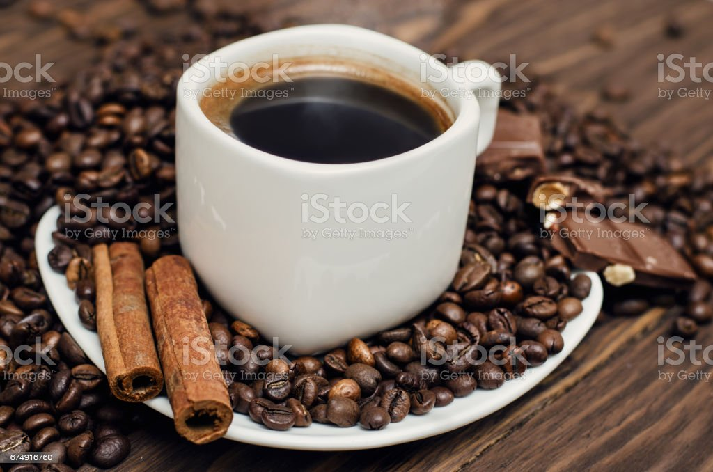 Coffee cup with beans and cinamon on a wooden table stock photo