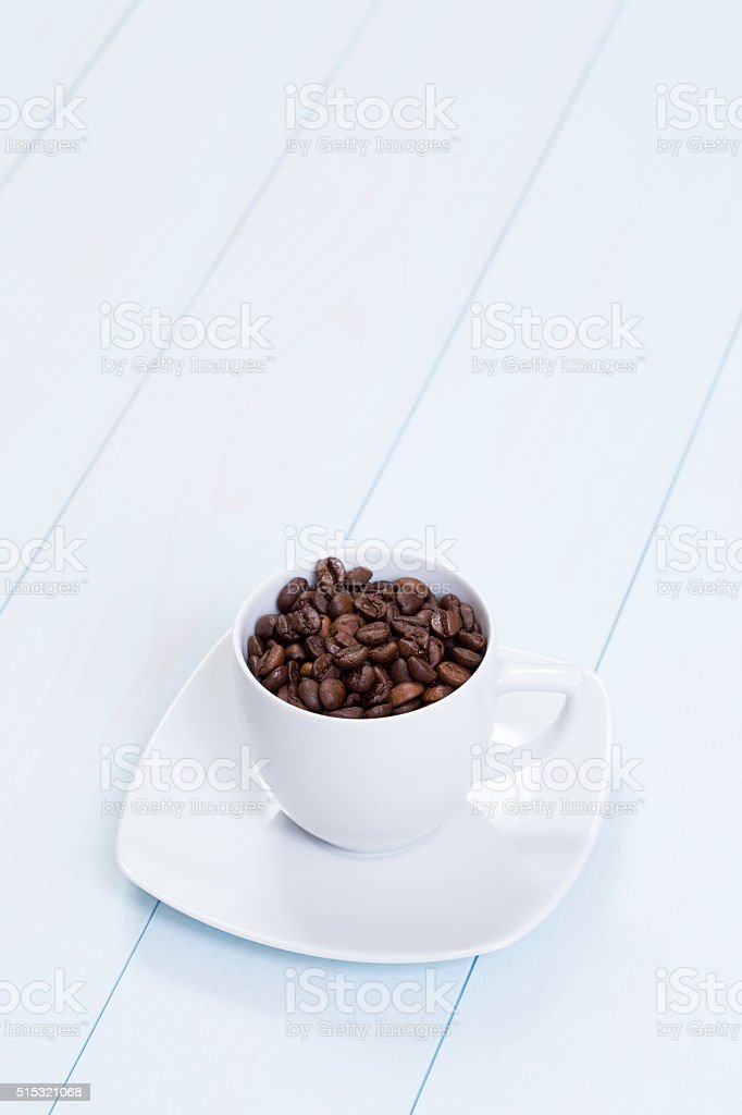 Coffee cup with coffee beans on table stock photo