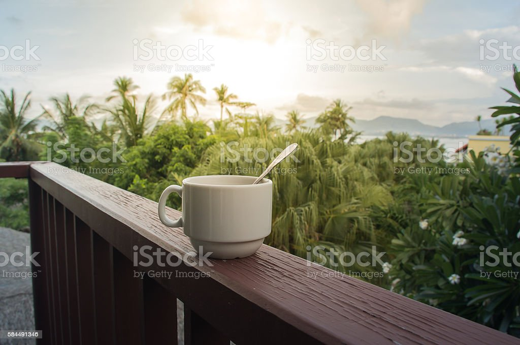 Coffee cup with coffee spoon on the wooden balcony stock photo