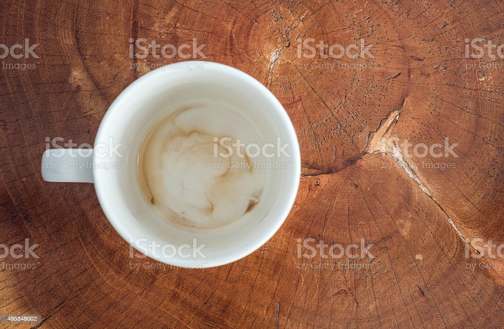 Coffee cup with coffee stain at bottom on wooden background stock photo