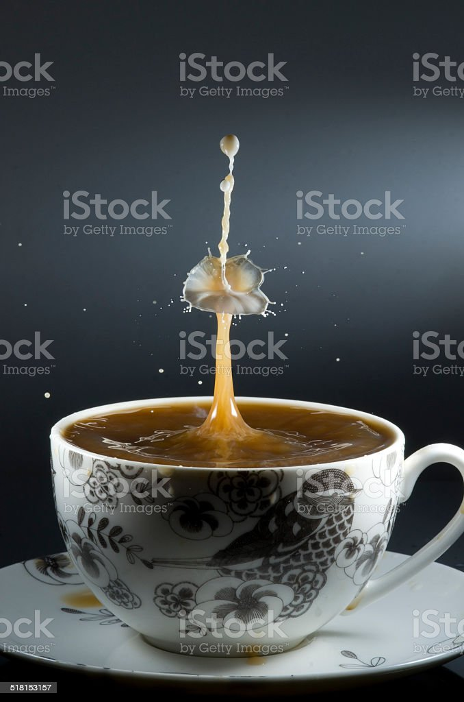Coffee cup with drop of milk landing in the coffee stock photo