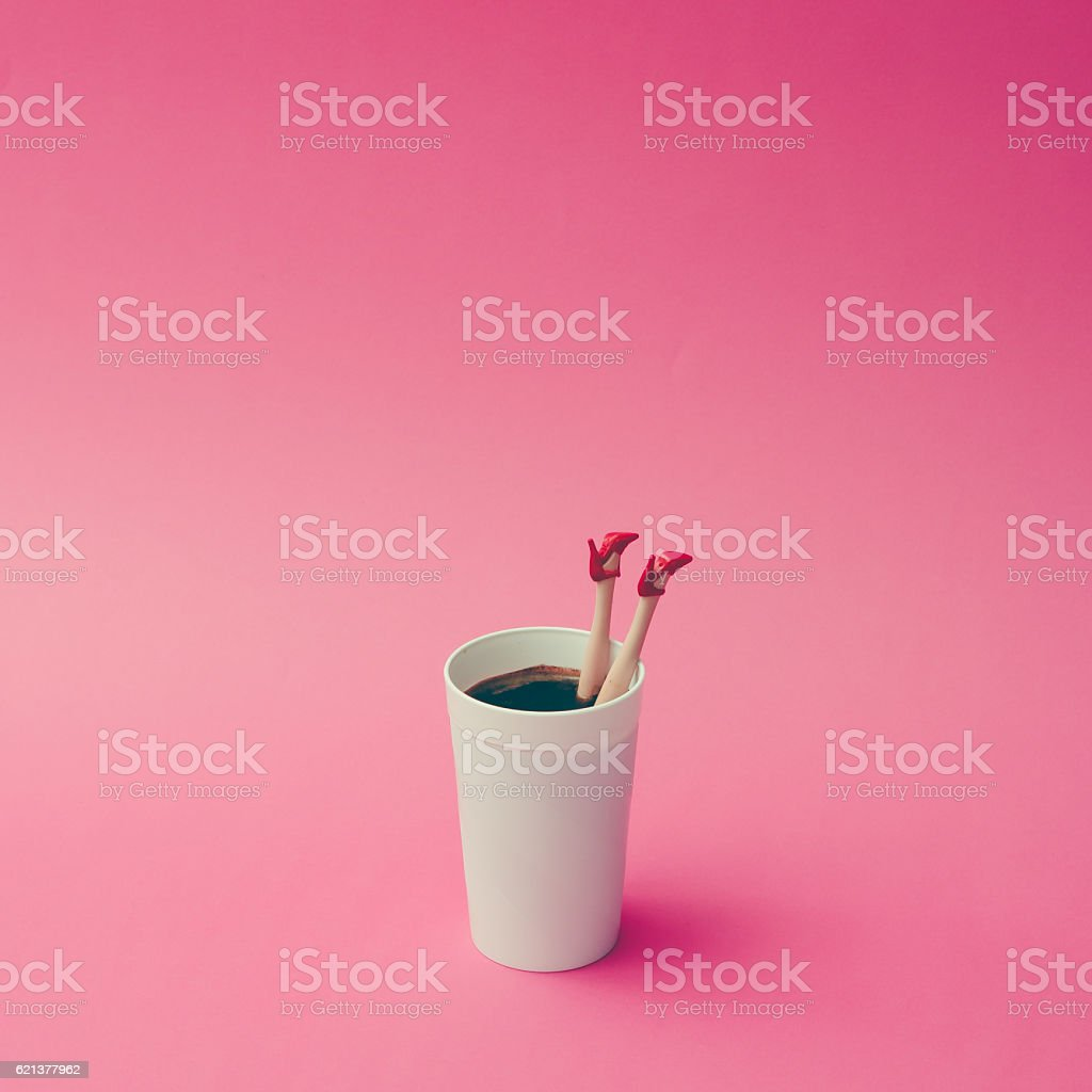 Coffee cup with female doll legs on pink background. stock photo
