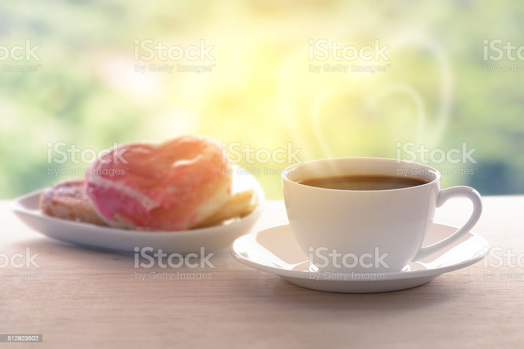 Coffee cup with heart shaped smoke and donut background. stock photo
