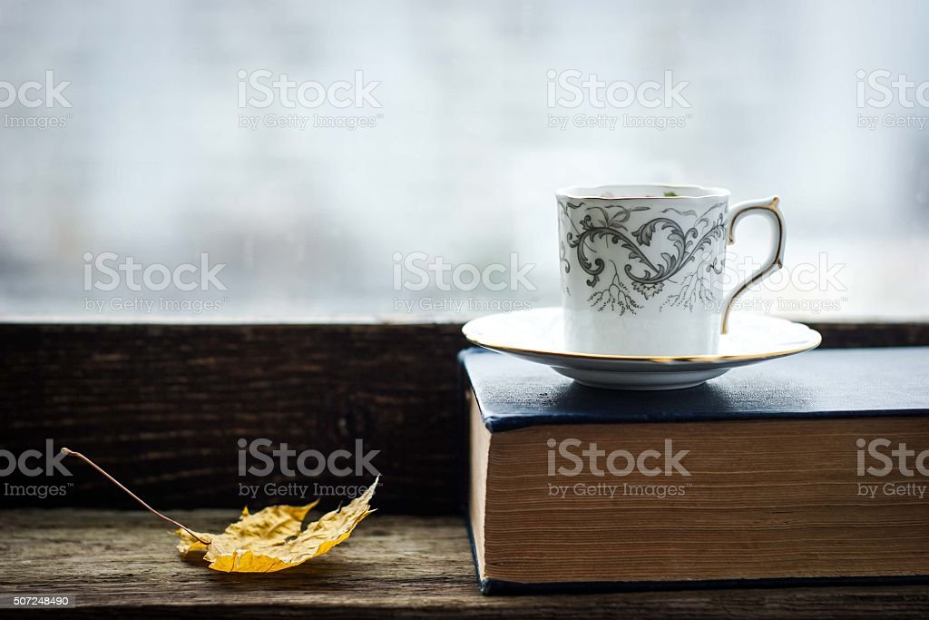 Coffee cup  with maple leaf  and old book stock photo