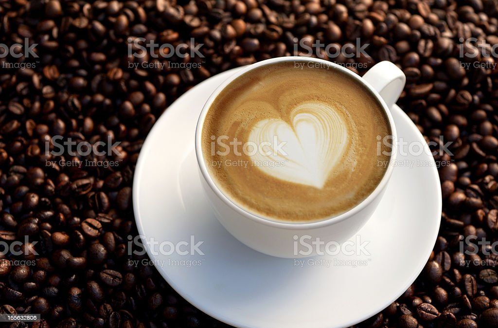 Coffee cup with milk heart on coffee beans royalty-free stock photo