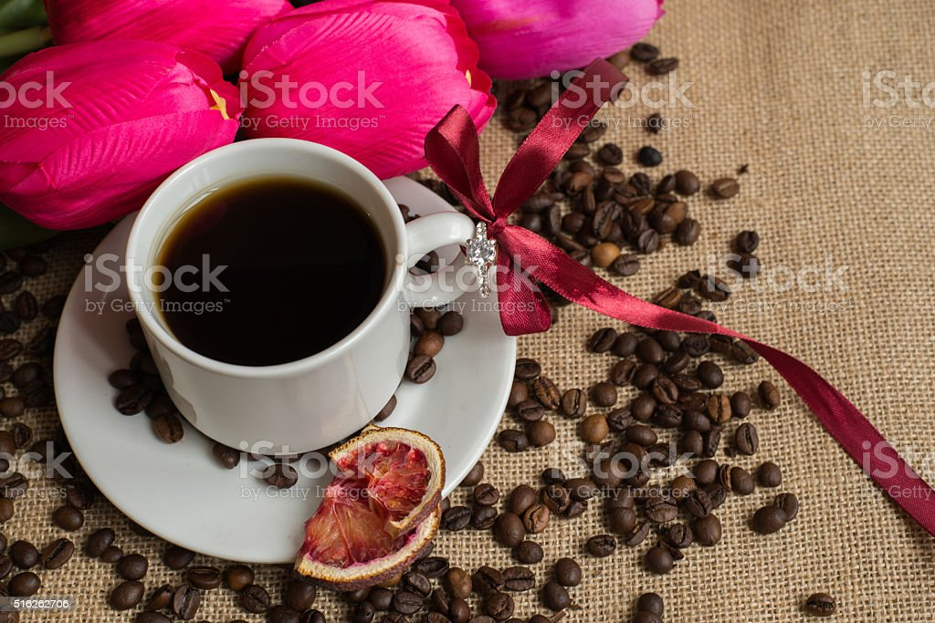 Coffee cup with raw beans on burlap with pink tulips stock photo