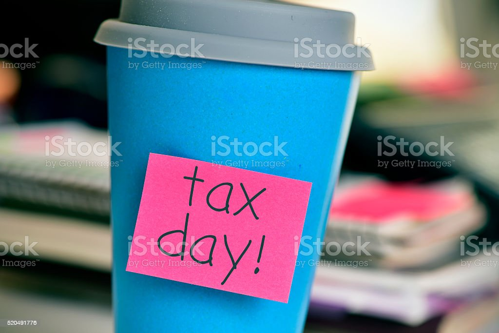 coffee cup with the text tax day in the office stock photo
