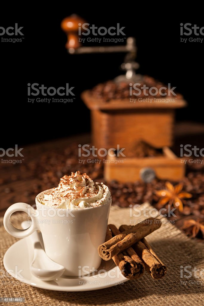 Coffee cup with whipped cream and coffee grinder on background stock photo