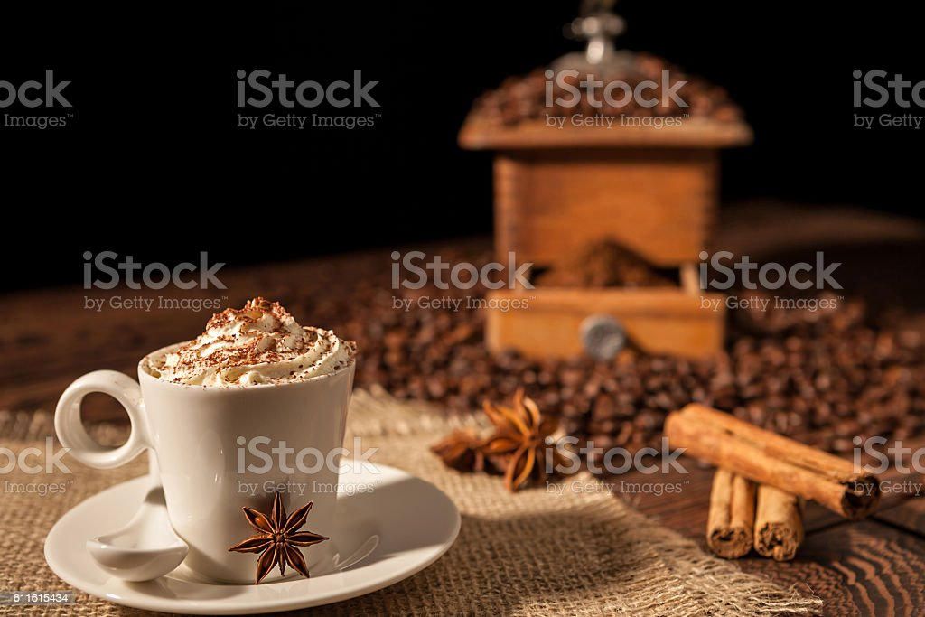 Coffee cup with whipped cream, cocoa powder and star anise stock photo