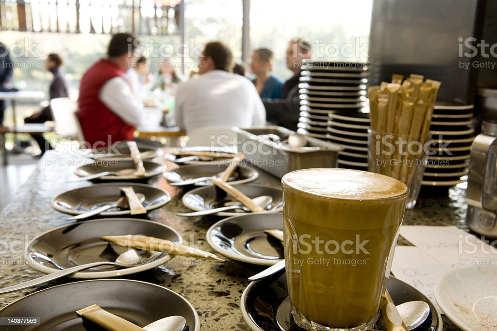 coffee cups and saucers at cafe with people in background royalty-free stock photo