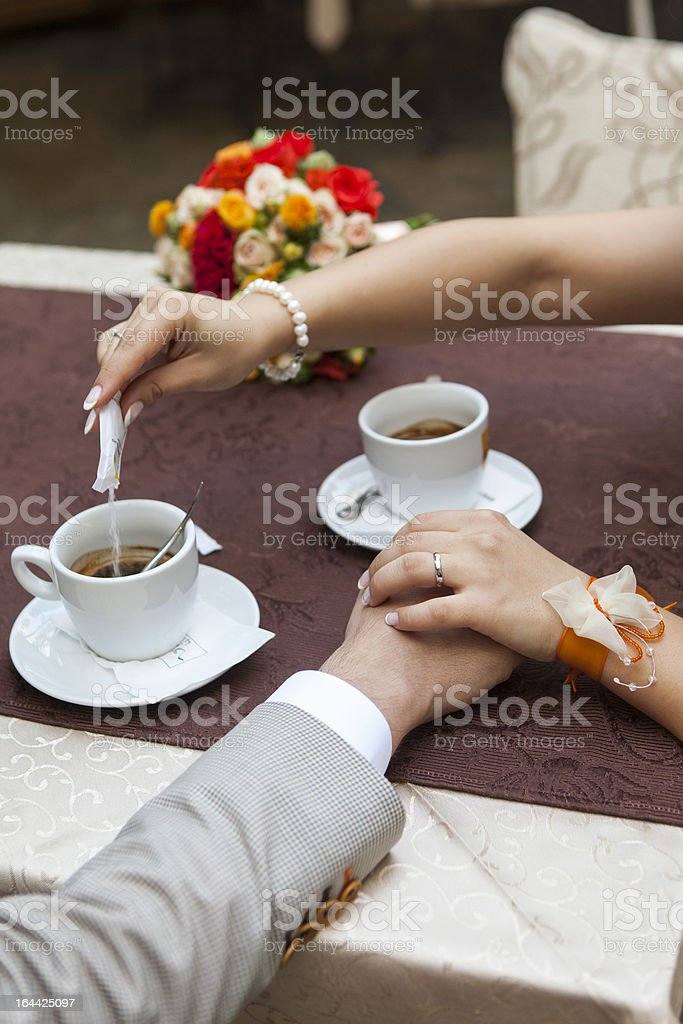 Coffee cups holding hands and putting suger in coffe stock photo