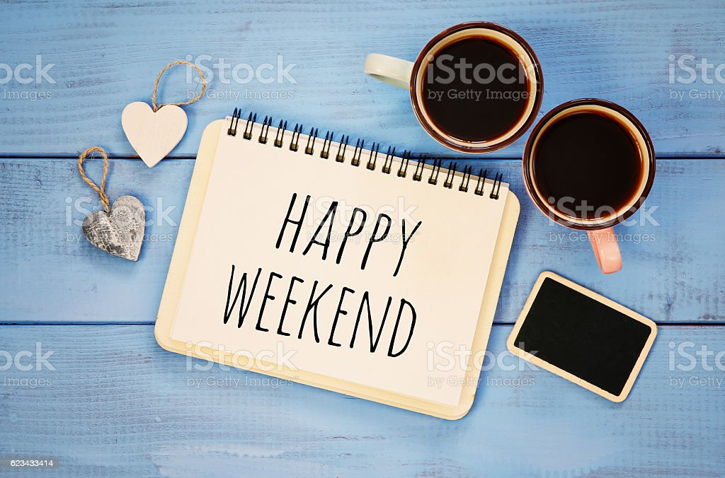 coffee cups next to notebook with phrase 'happy weekend' stock photo