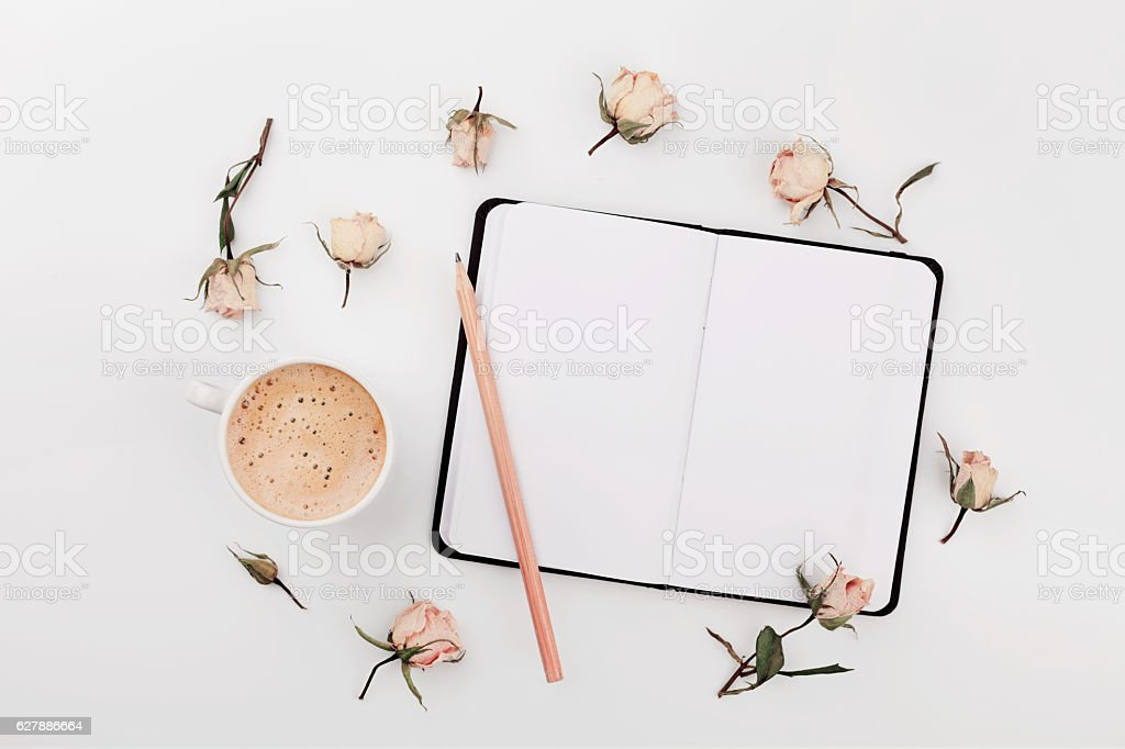 Morning Cup of coffee, empty notebook and dry roses flowers on white...