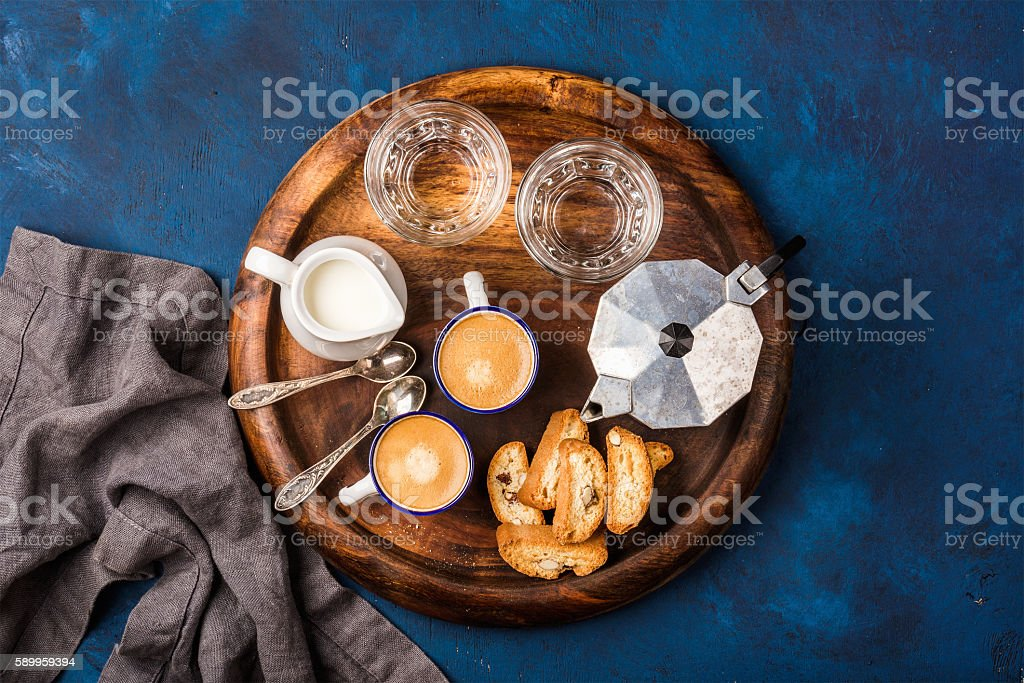 Coffee espresso, cantucci, cookies, milk and water on wooden board stock photo