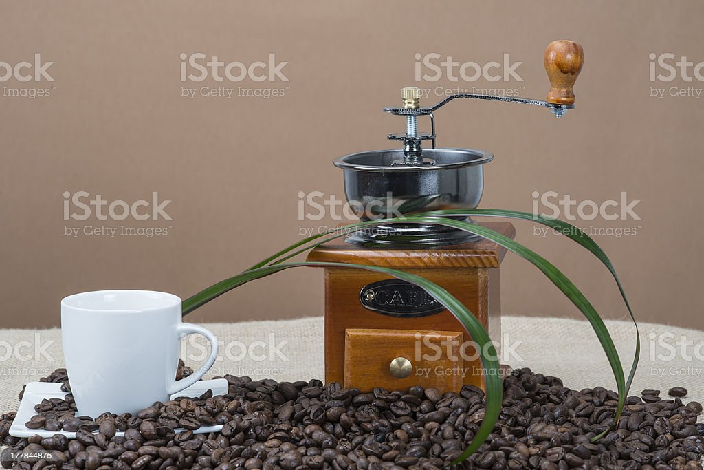 Coffee grinder and cups on some beans royalty-free stock photo