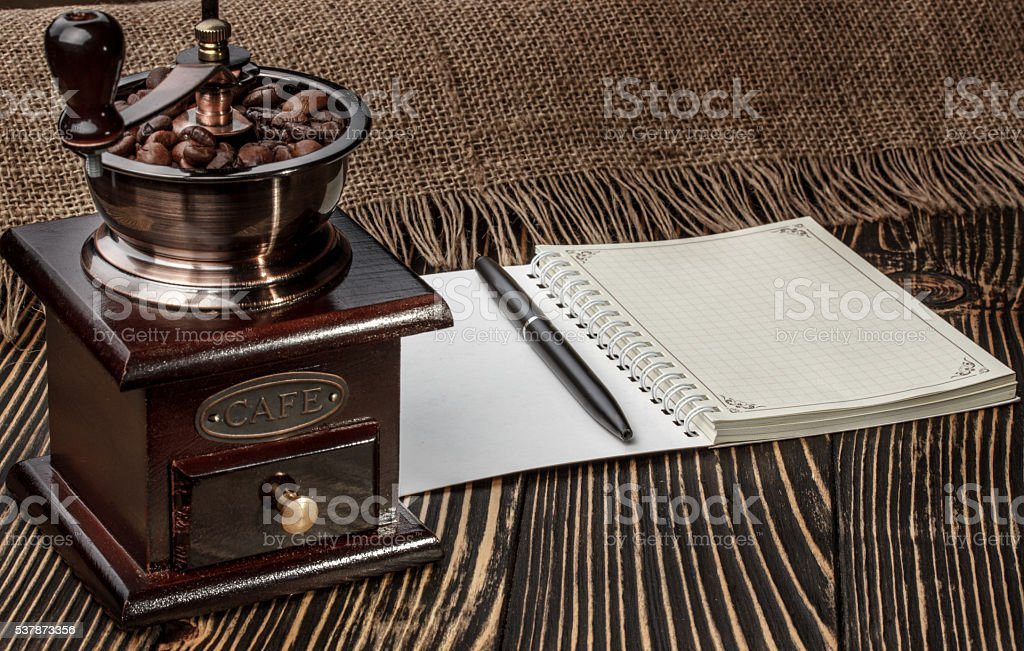 Coffee grinder and notebook on old wooden desk stock photo