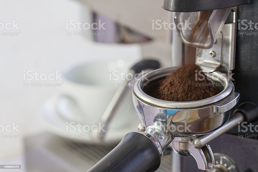 coffee grinder grinding freshly roasted coffee beans into a coff stock photo