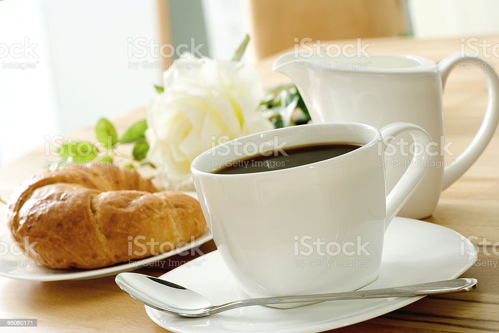 Coffee in a cup and a saucer and a fresh croissant royalty-free stock photo